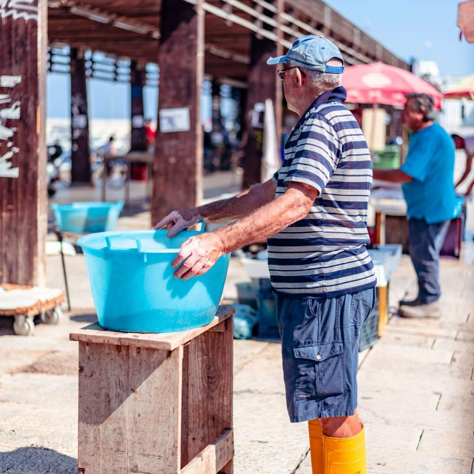 Fisherman with yellow boots at the fish market at the jetty Saint Nicholas in Bari